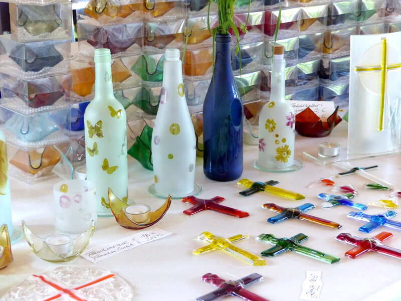Glasmalerei Sattler - Glasaccessoires im Überblick, Teelichter aus Glas, Kreuze aus Glas in verschiedenen Farben, besondere Glaskunstflaschen