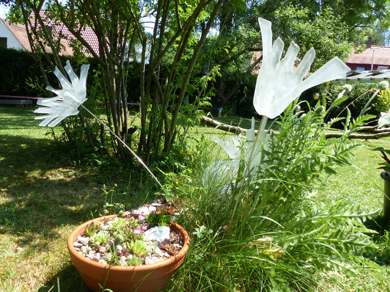 Die Glasmalerei Sattler stellt viele schöne Accessoires aus Glas her, hier ein Beispiel für den Garten. schwingende Glaselemente in weiß als besonders haltbarer Schmuck und Zierde für die Augen.