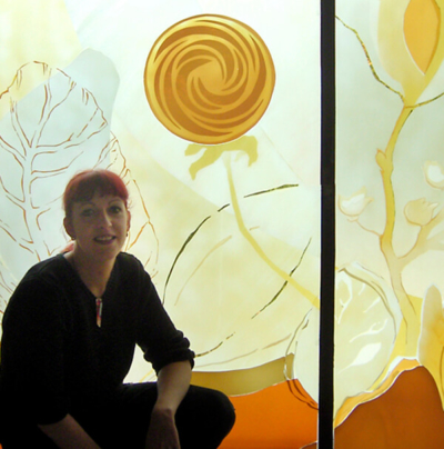 Katrin Engel-Meyer von der Glasmalerei Sattler sitzt vor dem Fenster der Kapelle in Argenbühl
